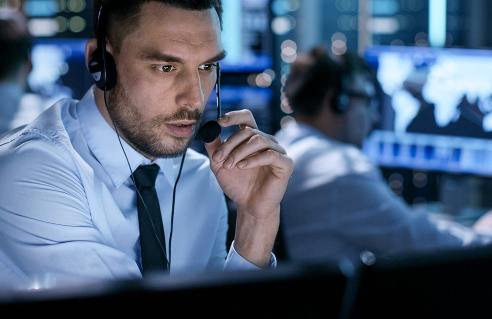 Private security consultant in a control room carrying out employee manpower surveillance monitoring and investigations in UK