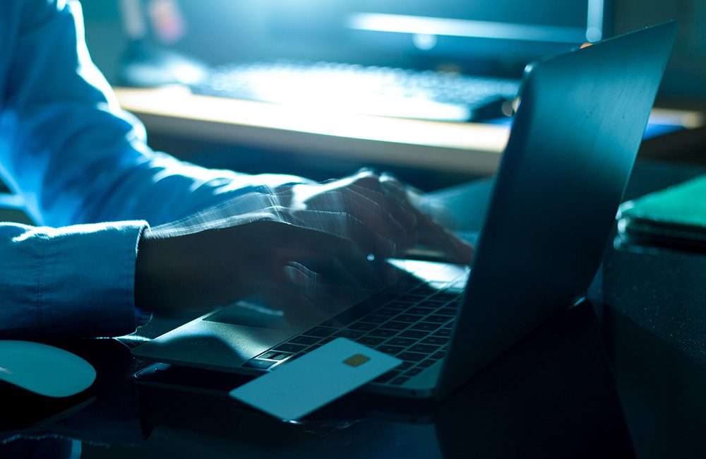 Private investigator working at his laptop to solve a theft burglary investigation in the UK