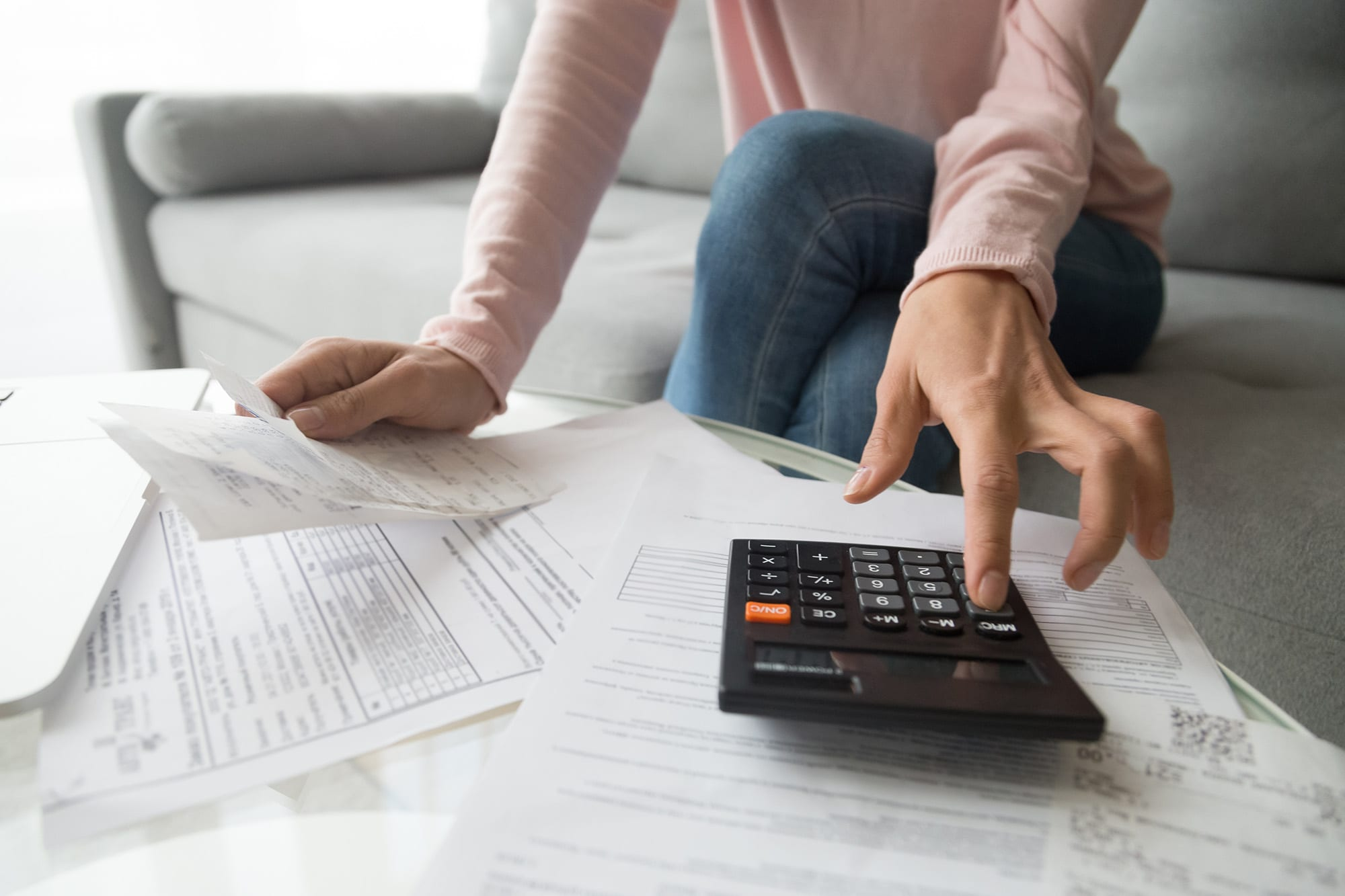 A young lady at home trying to calculate the costs and pricing for a small self-administered scheme SSAS